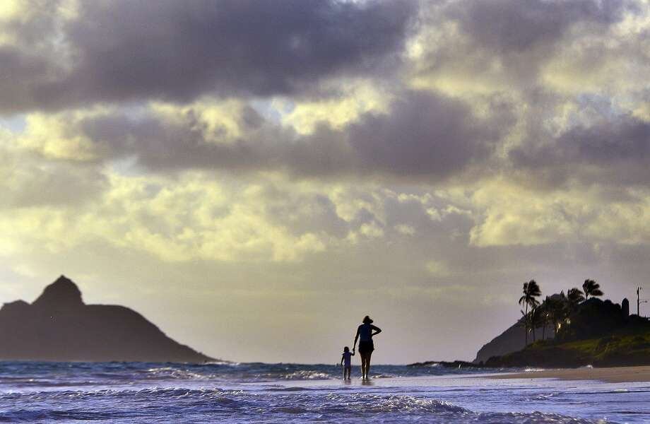 Anne Kllingshirn of Kailua, Hawaii walks with her daughter Emma, 1, as storm clouds are are seen during the sunrise hours on Kailua Beach, in Kailua, Hawaii, Thursday morning Aug. 7, 2014 . Hurricane Iselle is expected to arrive on the Big Island on Thursday evening, bringing heavy rains, winds gusting up to 85 mph and flooding in some areas. Weather officials changed their outlook on the system Wednesday after seeing it get a little stronger, giving it enough oomph to stay a hurricane as it reaches landfall. (AP Photo/Luci Pemoni) Photo: Luci Pemoni, Associated Press