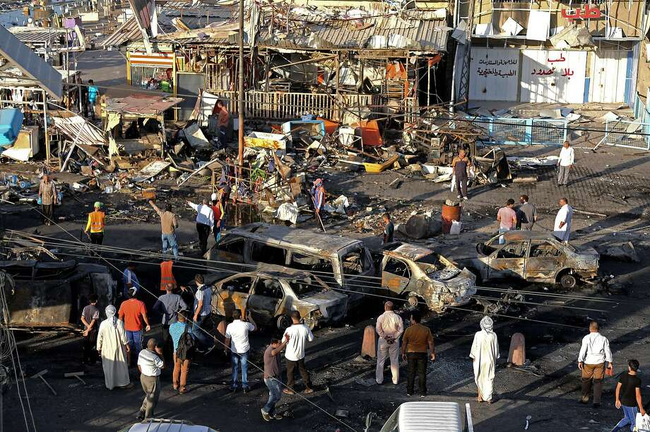 Baghdad residents gather after a series of car bombs tore through busy shopping streets in several neighborhoods, killing at least 50 people. Photo: Karim Kadim, Associated Press