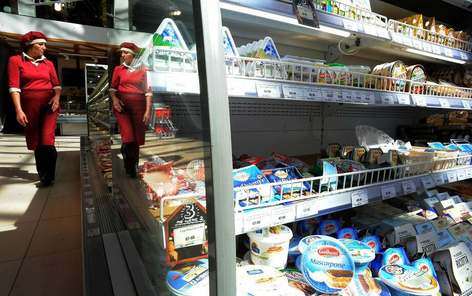 A Russian woman walks past refrigerated foodstuffs at a supermarket in Saint Petersburg on August 7, 2014. Russia retaliated against tough new Western sanctions, banning most food imports from the United States and the European Union and threatening to block flights over its airspace. The tit-for-tat moves further heighten tensions between Russia and the West over the conflict in Ukraine, where heavy shelling was reported in the rebel-held eastern city of Donetsk. AFP PHOTO / OLGA MALTSEVAOLGA MALTSEVA/AFP/Getty Images Photo: Olga Maltseva, AFP/Getty Images