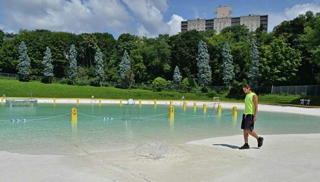 Lifeguard supervisor Brenen Foster checks on water levels as the Lincoln Park pool is refilled after being closed temporarily while crews drained the water after recent heavy and damaging storms Thursday August 7, 2014, in Albany, NY.   (John Carl D'Annibale / Times Union) Photo: John Carl D'Annibale / 00028072A
