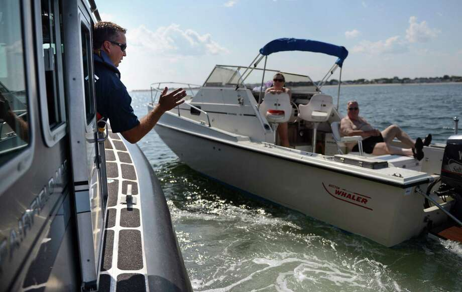 Officer James Wiltsie stops to talk to Beth and Doug McCaskey, of Fairfield, as he parols the Long Island Sound off of Jennings Beach in Fairfield, Conn., Thursday, Aug. 7, 2014. Photo: Autumn Driscoll / Connecticut Post