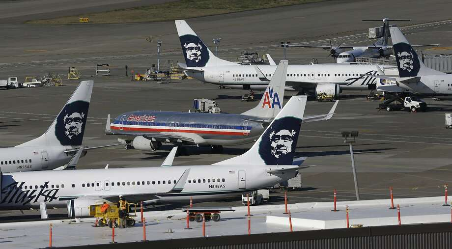 An American Airlines plane taxis near a group of planes from Alaska Airlines, Monday, Oct. 28, 2013, at Seattle-Tacoma International Airport in Seattle.  Photo: Ted S. Warren, Associated Press