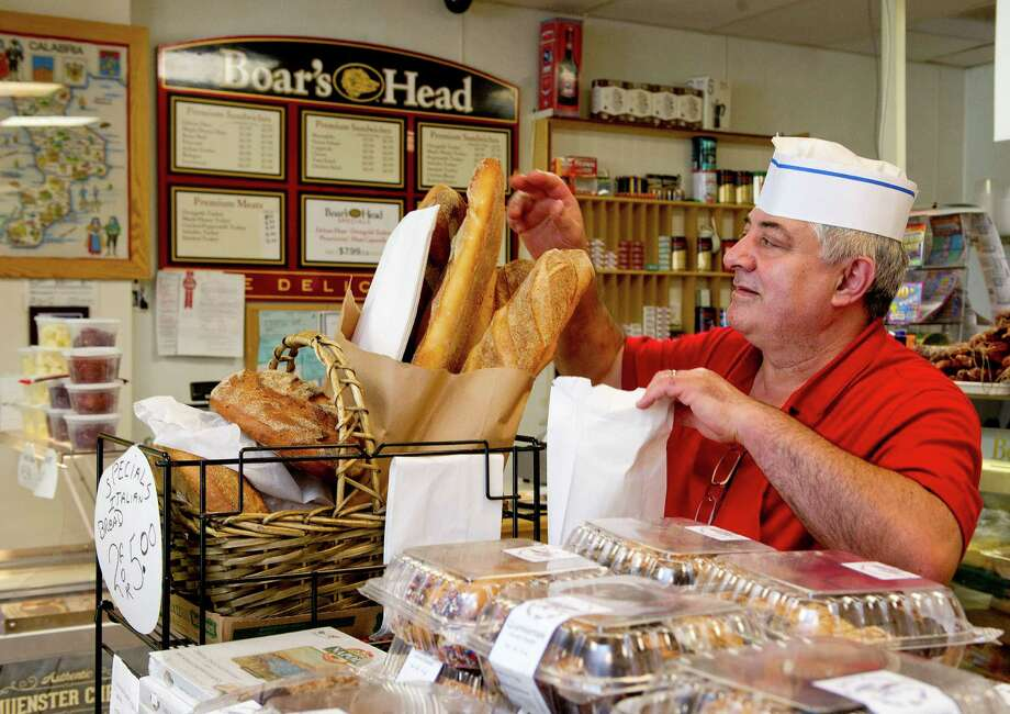 Joe Fusaro bags Italian bread at Fusaro's Deli and Market on High Ridge Road in Stamford, Conn., on Thursday, August 7, 2014. The store is celebrating its 25th anniversary. Photo: Lindsay Perry / Stamford Advocate