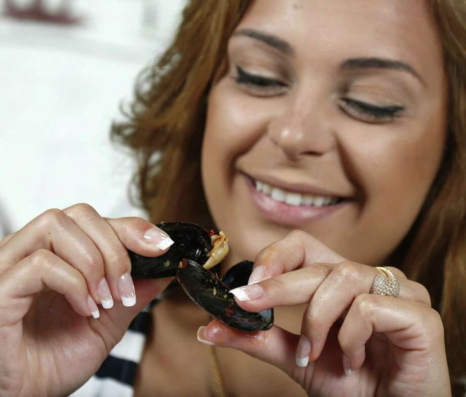 Model Eve Korun demonstrates how to use one empty mussel shell as a tong to eat the others at La Frite in Southtown. Photo: William Luther, San Antonio Express-News / © 2014 San Antonio Express-News