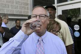 Toledo Mayor D. Michael Collins drinks a glass of tap water after a news conference in Toledo, Ohio, Monday, Aug. 4, 2014. A water ban that had hundreds of thousands of people in Ohio and Michigan scrambling for drinking water has been lifted, Collins announced Monday. (AP Photo/Paul Sancya)