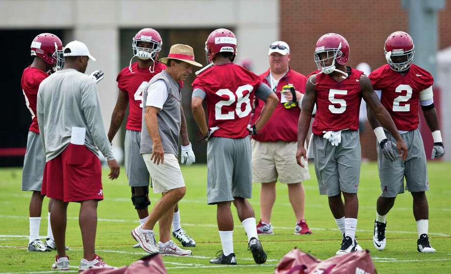 Alabama head coach Nick Saban (center) stands with Crimson Tide defensive backs Anthony Averett (No. 28), Cyrus Jones (No. 5) and former Ozen star Tony Brown (No. 2) during a practice on Friday, Aug. 1, 2014, in Tuscaloosa, Ala. (AP Photo/Brynn Anderson) Photo: Brynn Anderson, STF / AP
