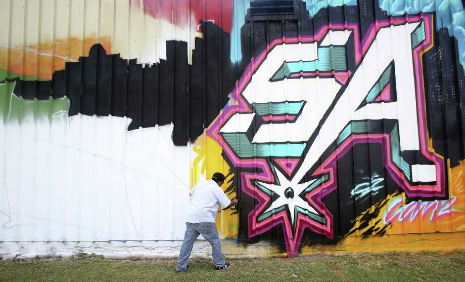 "Henry Cantu, known as Can2, works on the wall at the Gillette Air Conditioning Co. building  off I-10 between Fulton and Hildebrand avenues. He is inviting the public to bring their children to ""finish"" his work with their own aerosol art. Photo: Photos By Helen L. Montoya / San Antonio Express-News / ©2014 San Antonio Express-News"