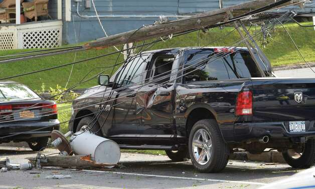 A severely damage pickup truck sits under power lines on Broad Street as a result of storm damage Thursday evening, Aug. 7, 2014 in Schuylerville, N.Y.  (Skip Dickstein/Times Union) Photo: SKIP DICKSTEIN