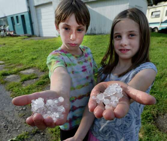 Elliott Woods, 9, stands with his sister Katherine Woods, 7, holding hailstones that they gathered following a storm Thursday evening, Aug. 7, 2014, in Schuylerville, N.Y.  (Skip Dickstein/Times Union) Photo: SKIP DICKSTEIN