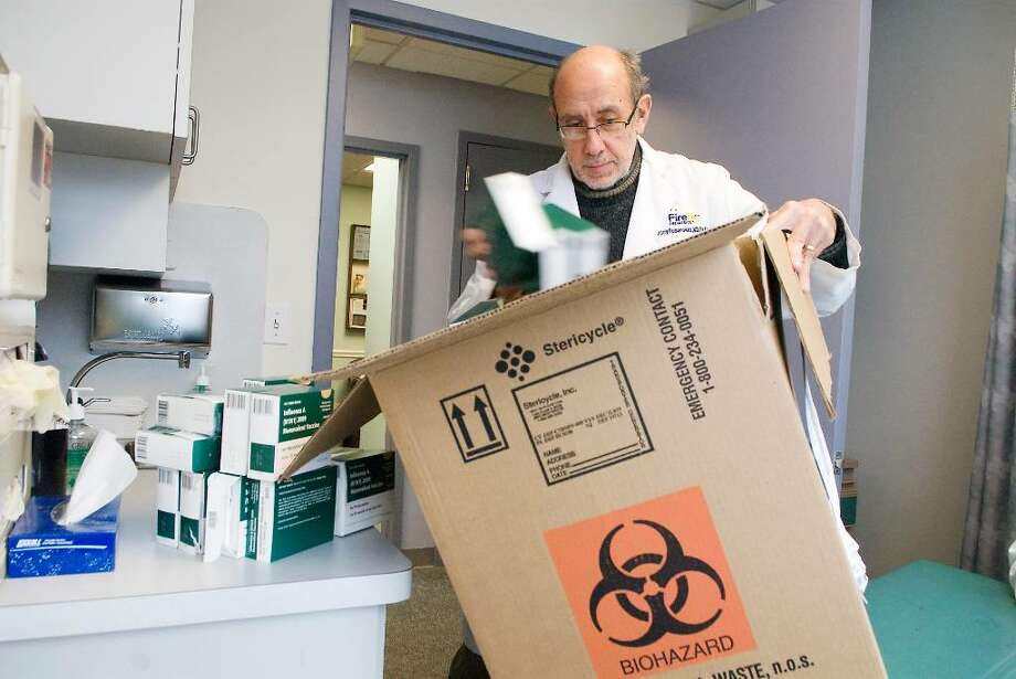 Dr. Harry Romanowitz, medical director of Firefly After Hours Pediatric, disposes of H1N1 flu vaccines in Stamford, Conn. on Tuesday, Feb. 16, 2010.  The manufacturer Sanofi Pastuer recalled the vaccine lots after the vaccination's potency dipped below the ideal strength. Photo: Kathleen O'Rourke / Stamford Advocate
