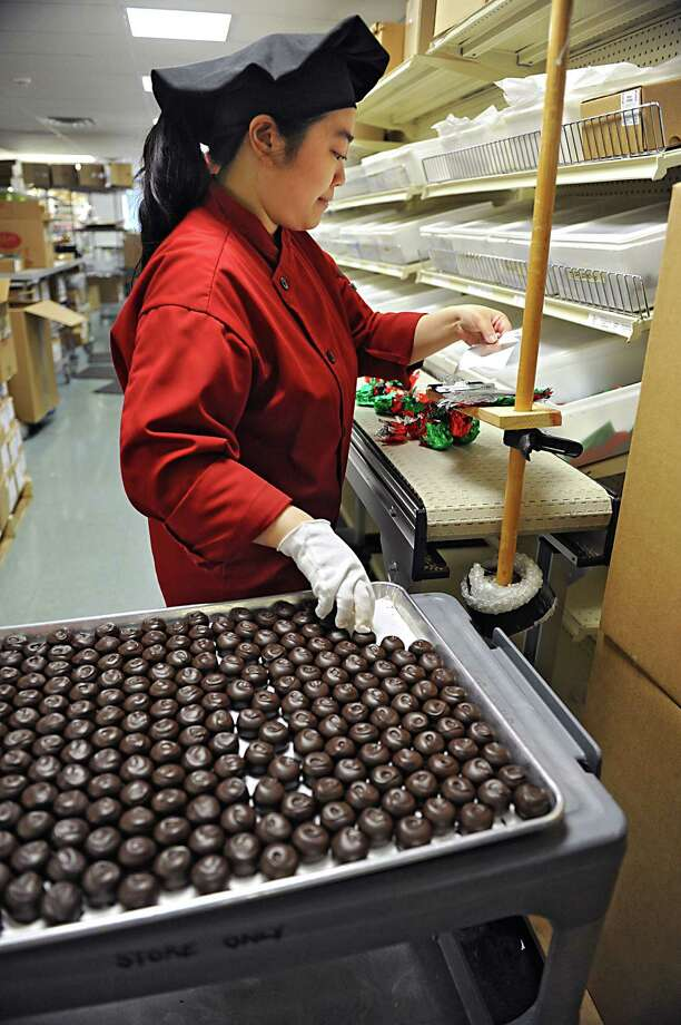 Employee Ivy Chenon packages truffles at Krause's Homemade Candy Store on Thursday, Aug. 7, 2014 in Colonie, N.Y. Two homes will be demolished next to Krause's so the candy store can create a packaging business next to the store. (Lori Van Buren / Times Union) Photo: Lori Van Buren / 00028074A