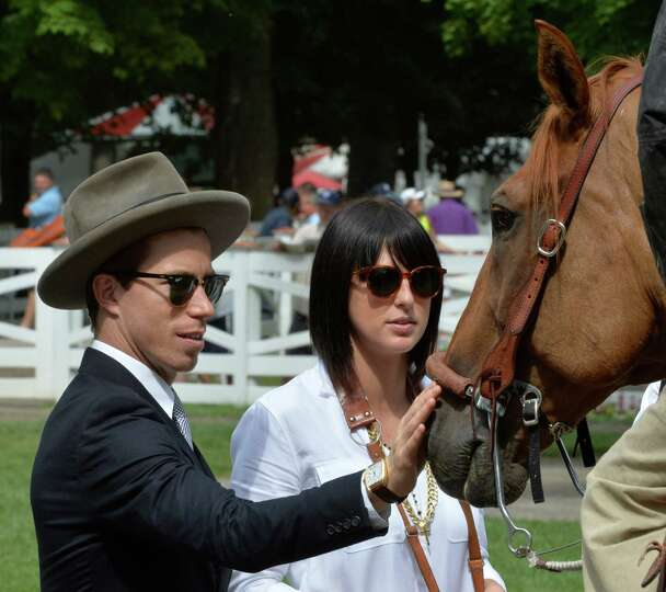 Olympic gold medalist Shawn White, left, gives a friendly pat on the nose to an outrider's horse Thu