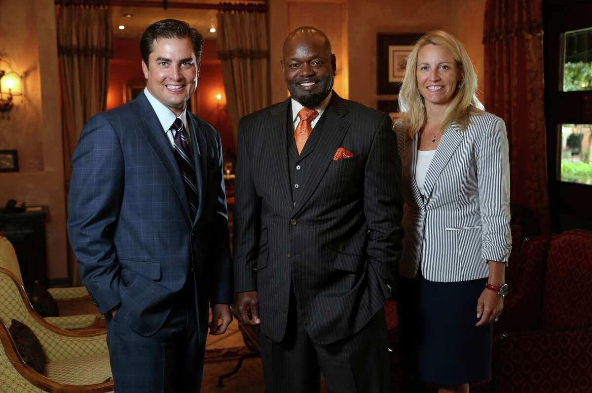 Emmitt Smith, chairman of E Smith Realty, is flanked by Brant Landry, president and chief operating officer, and Sharon Morrison, chief executive officer.