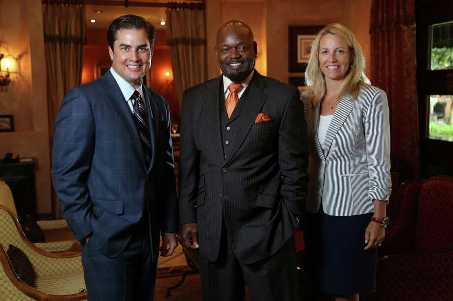 Emmitt Smith, chairman of E Smith Realty, is flanked by Brant Landry,  president and chief operating officer, and Sharon Morrison, chief executive officer. Photo: Gary Coronado, Staff / © 2014 Houston Chronicle