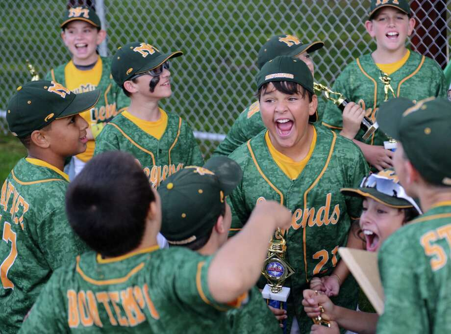 New Milford's Jack Hayes (21) celebrates with teammates after his team's 4-3 win over Exeter, N.H. in the Cal Ripken baseball league 11 year old, 70' diamond regional championship game at Glander Field Complex in Newtown, Conn. Thursday, Aug. 7, 2014. Photo: Tyler Sizemore / The News-Times
