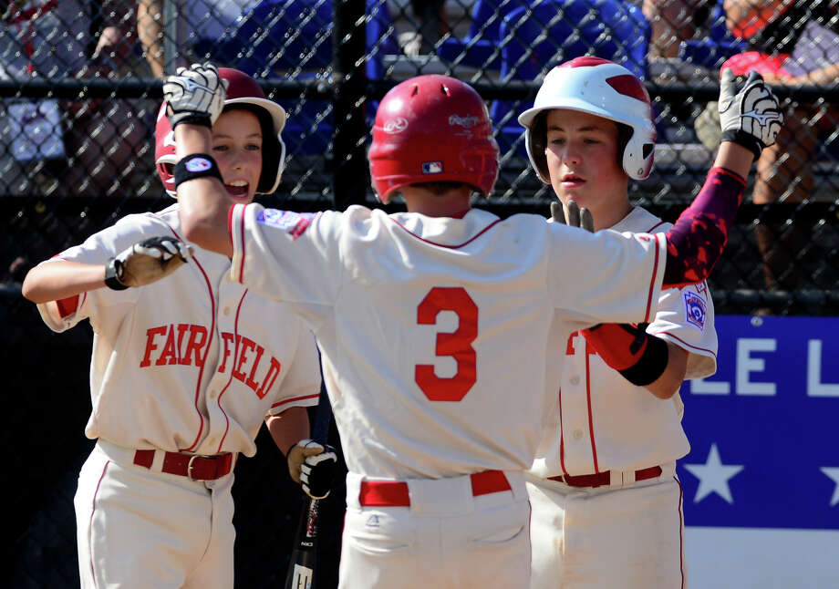 Fairfield American's Brian Howell, center, reaches out to hug his teammates at home plate after hitting a home run, during the New England Regional Little League semi-final action against Massachussetts in Bristol, Conn. on Thursday, Aug. 7, 2014. Fairfield went on to win the game 9-0 and will face Rhode Island in the series final on Saturday. Photo: Christian Abraham / Connecticut Post