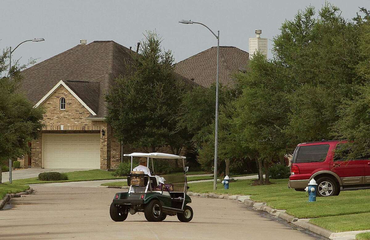A golf cart drives down the street in the Heritage Grand 55& subdivision in Cinco Ranch on Thursday, July 31, 2014, in Houston. Golf carts are a common choice of transportation in the 55& community. ( J. Patric Schneider / For the Chronicle )