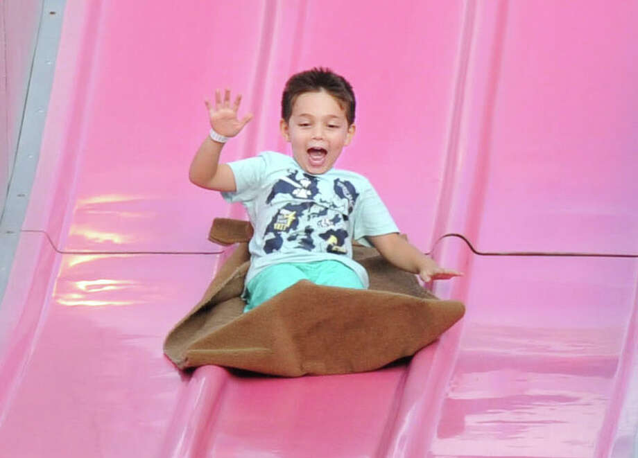 Hudson Burchetta, 5, of Greenwich, enjoys the big slide during the St. Roch Church Feast on St. Roch Avenue in the Chickahominy section of Greenwich, Conn., Thursday night, Aug. 7, 2014. The feast and carnival's last night is Saturday evening from 6 p.m. to 10:30 p.m. Photo: Bob Luckey / Greenwich Time