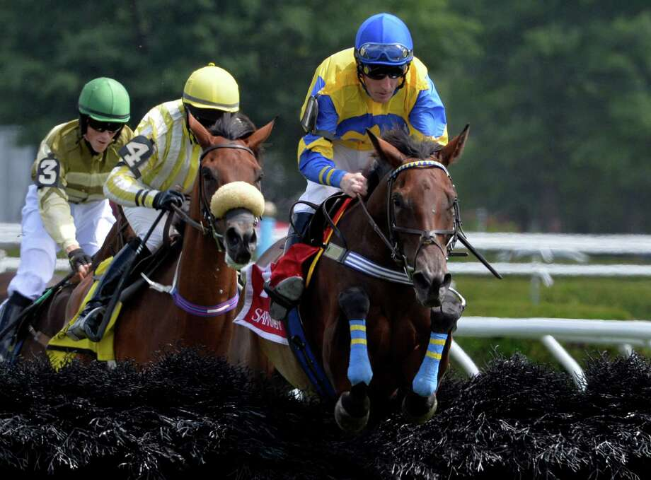 Cat Feathers with jockey Bernard Dalton flies over the final fence on the way to the win in The Mrs. Ogden Phipps Stakes steeplechase Thursday, Aug. 7, 2014, at Saratoga Race Couse in Saratoga Springs, N.Y.    (Skip Dickstein/Times Union) Photo: SKIP DICKSTEIN