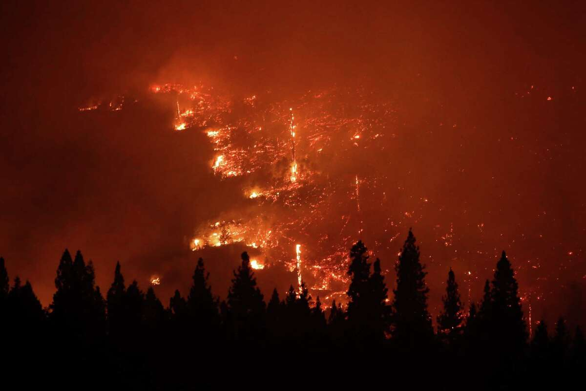 In this Aug. 24, 2013 file photo, a forest smolders as the Rim Fire continues to burn near Yosemite National Park, Calif. Keith Matthew Emerald was charged Thursday, Aug. 7, 2014 with starting the state's third-largest wildfire, a 2013 blaze that charred hundreds of square miles of land in Yosemite National Park and the Stanislaus National Forest.