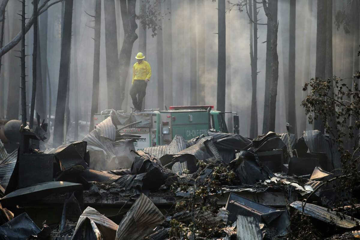 In this Aug. 26, 2013 file photo, a firefighter stands on top of a fire truck at a campground destroyed by the Rim Fire near Yosemite National Park, Calif. Keith Matthew Emerald was charged Thursday, Aug. 7, 2014 with starting the state's third-largest wildfire, a 2013 blaze that charred hundreds of square miles of land in Yosemite National Park and the Stanislaus National Forest.