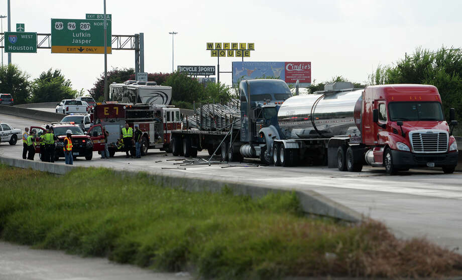 A collision between two 18-wheelers and another vehicle left traffic at a standstill Thursday afternoon. One of the 18-wheelers leaked some of its acidic cargo onto the roadway, prompting officials to shut down the entire section of highway. The Texas Department of Transportation estimated that the highway would be shutdown until past midnight. Photo taken Thursday 8/7/14 Jake Daniels/@JakeD_in_SETX Photo: Jake Daniels/@JakeD_in_SETX / ©2014 The Beaumont Enterprise/Jake Daniels