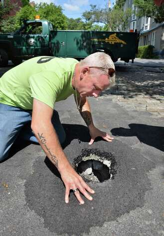 Jeff Kelley of the Albany Water Department  peers into a small opening above a 13'x13'x13' deep sinkhole on Jay Street at Dove Thursday Aug. 7, 2014, in Albany, N.Y.  (John Carl D'Annibale / Times Union) Photo: John Carl D'Annibale / 10028086A