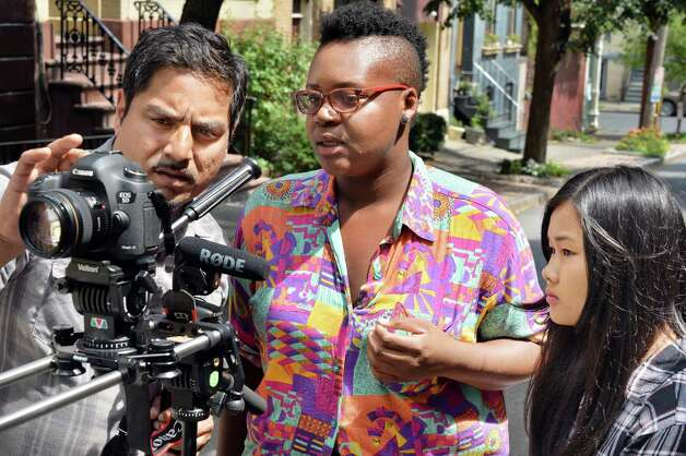 YouthFX program director Bhawin Suchak, left, works on camera techniques with students Darian Henry, 21, and Sayblu Htoo, 17, right, all of Albany, on Elm Street Thursday August 7, 2014, in Albany, NY. Film eXperience is a 6-week summer program where youth ages 14 to 18 learn about what it takes to make movies. (John Carl D'Annibale / Times Union) Photo: John Carl D'Annibale / 00028069A