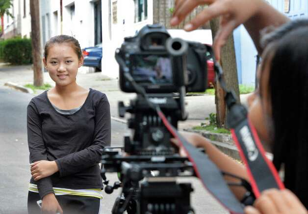 YouthFX student Yad Na, 16, left, of Albany, spends some time in front of the camera during a location shoot on Elm Street Thursday August 7, 2014, in Albany, NY. Film eXperience is a 6-week summer program where youth ages 14 to 18 learn about what it takes to make movies. (John Carl D'Annibale / Times Union) Photo: John Carl D'Annibale / 00028069A