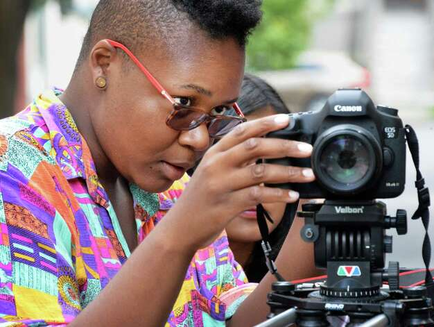 YouthFX student Darian Henry, 21, of Albany, adjusts camera settings during a location shoot on Elm Street Thursday August 7, 2014, in Albany, NY. Film eXperience is a 6-week summer program where youth ages 14 to 18 learn about what it takes to make movies. (John Carl D'Annibale / Times Union) Photo: John Carl D'Annibale / 00028069A