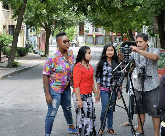 YouthFX program director Bhawin Suchak, right, works on camera techniques with students, from left, Darian Henry, 21, Rama Be, 14, and Sayblu Htoo, 17, right, all of Albany, on Elm Street Thursday August 7, 2014, in Albany, NY. Film eXperience is a 6-week summer program where youth ages 14 to 18 learn about what it takes to make movies. (John Carl D'Annibale / Times Union) Photo: John Carl D'Annibale / 00028069A