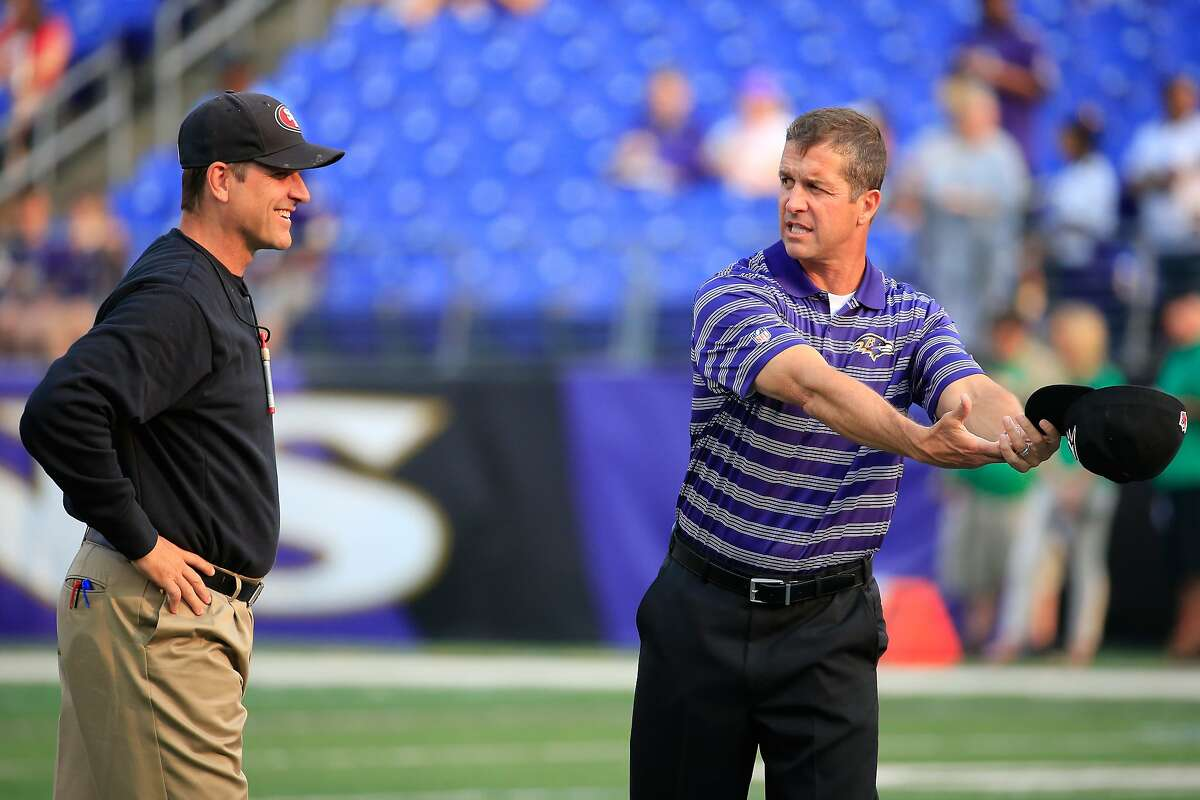 BALTIMORE, MD - AUGUST 07: Head coach Jim Harbaugh of the San Francisco 49ers (L) and his brother head coach John Harbaugh of the Baltimore Ravens talk before the start of their NFL pre-season game at M&T Bank Stadium on August 7, 2014 in Baltimore, Maryland. (Photo by Rob Carr/Getty Images)