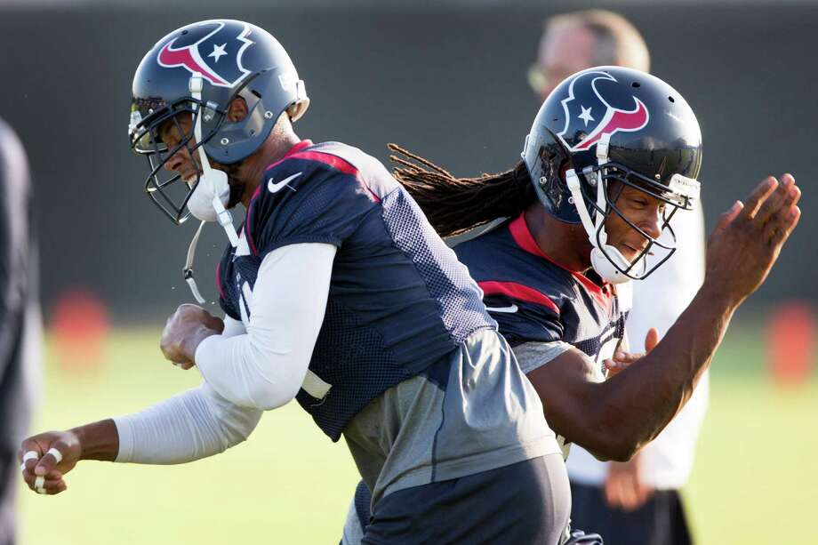 Texans wide receivers DeVier Posey, left, and DeAndre Hopkins cross paths as they run their routes during passing drills Thursday. Photo: Brett Coomer, Staff / © 2014 Houston Chronicle