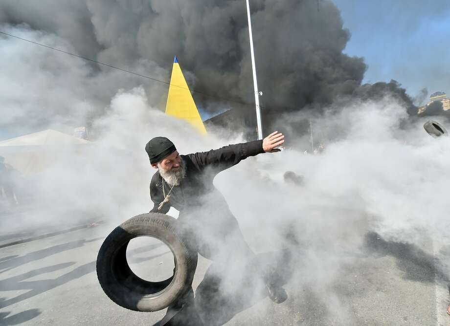 TOPSHOTS An Orthodox priest throws a tyre as Maidan self-defence activists clash with fighters of Kiev-1 volunteer battalion on Independence Square in Kiev on August 7, 2014. Kiev's municipal services protected with the servicemen tried to remove tents from the city's central Independence Square, also known as Maidan, and free Khreshchatyk Street for the traffic. Some few hundreds of Maidan activists still live in the tent camp set in the center of the Ukrainian capital that upsets the vast majority of the local residents. AFP PHOTO/ SERGEI SUPINSKYSERGEI SUPINSKY/AFP/Getty Images Photo: Sergei Supinsky, AFP/Getty Images