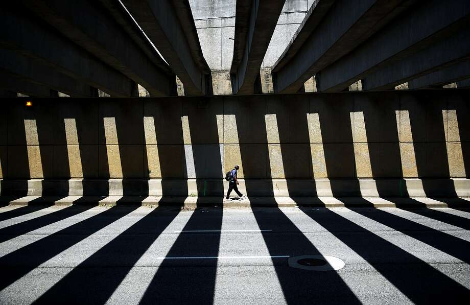 A pedestrian walks through a downtown underpass as the midday sun casts shadows from overhead beams, Thursday, Aug. 7, 2014, in Atlanta. (AP Photo/David Goldman) Photo: David Goldman, Associated Press