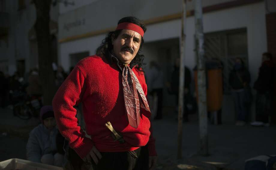 Angelito Ribero, poses for a photo dressed as 'Gauchito Gil,' a folk saint revered by Argentines, outside the San Cayetano church in Buenos Aires, Argentina, Thursday, Aug. 7, 2014. 'Gauchito Gil,' was an 1800's outlaw who became a mystical symbol of bravery; stealing from the rich and giving to the poor. Thousands of people visit the San Cayetano church, the patron saint of work, amid tough economic times in the South American country. (AP Photo/Natacha Pisarenko) Photo: Natacha Pisarenko, Associated Press