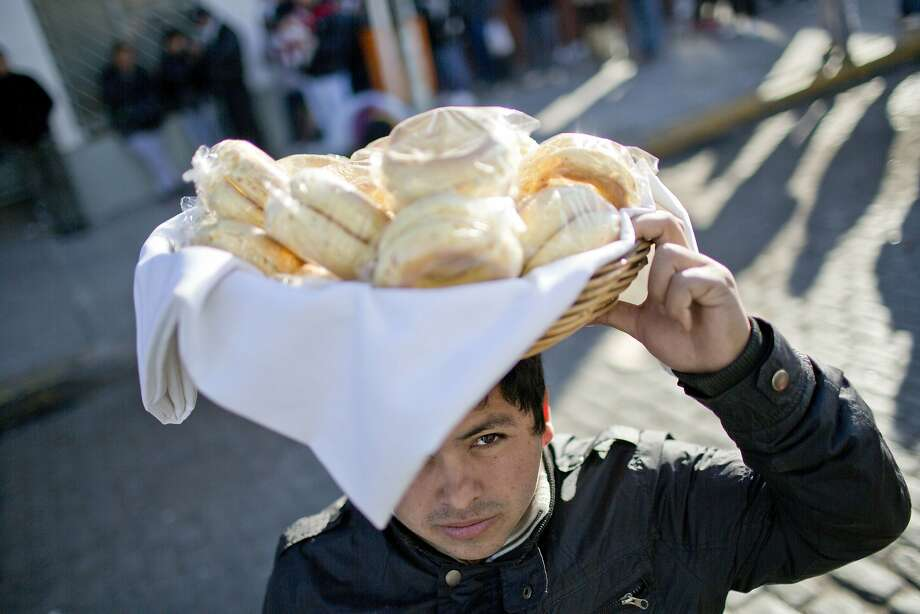 A young man sells bread outside the San Cayetano Catholic Church, in Buenos Aires, Argentina, Thursday, Aug. 7, 2014. An annual pilgrimage to the shrine of Saint Cayetano, the patron saint of work, has drawn thousands of Roman Catholics as the country faces difficult economic times. The 16th century Italian priest was born in 1480 in Vicenzia and became a priest at the age of 33. He died on Aug. 7, 1547. (AP Photo/Natacha Pisarenko) Photo: Natacha Pisarenko, Associated Press