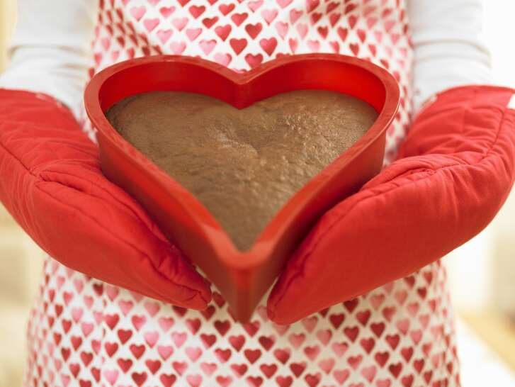 Close up of woman holding heart-shaped cake. baking cooking bake cook kitchen dessert heart valentine female kitchen