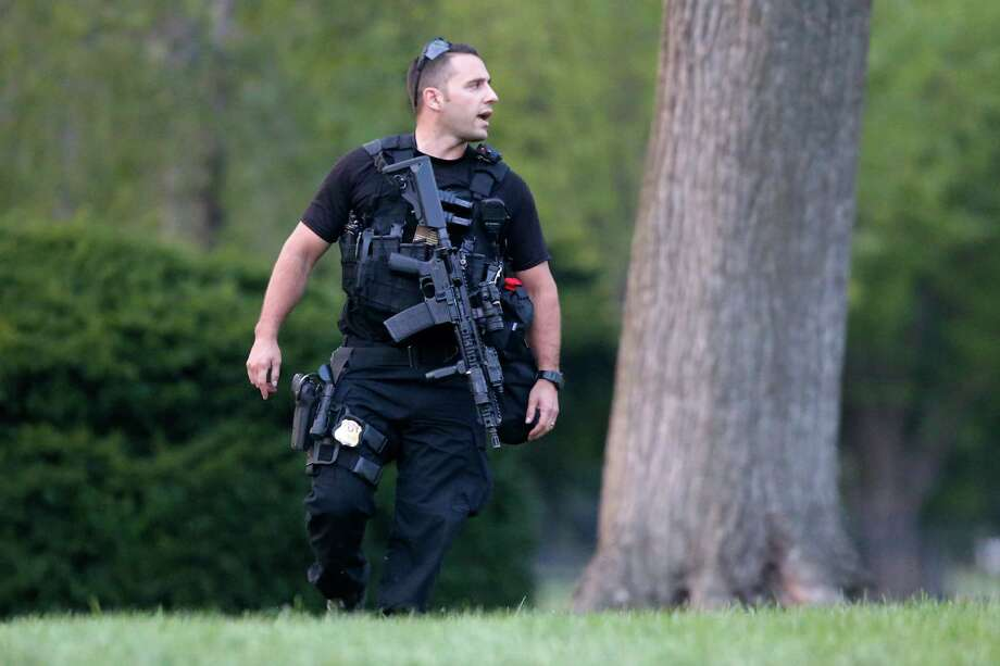A member of the U.S. Secret Service Emergency Response Team (ERT) stands watch on the North Lawn at the White House in Washington, Thursday, Aug. 7, 2014. It's usually someone jumping over the White House fence that causes Secret Service agents patrolling the grounds to scramble. A toddler passing through slats in the gate caught the eyes of the gun-toting officers who are charged with protecting the president. Photo: Charles Dharapak, AP / AP