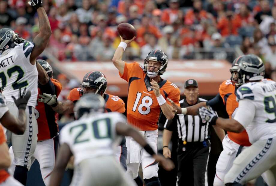Denver Broncos quarterback Peyton Manning (18) throws against the Seattle Seahawks during the first half of an NFL preseason football game, Thursday, Aug. 7, 2014, in Denver. (AP Photo/Joe Mahoney) Photo: AP