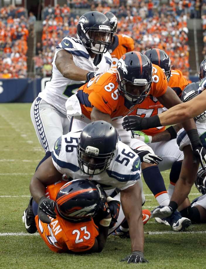 Denver Broncos running back Ronnie Hillman (23) scores a touchdown as Seattle Seahawks defensive end Cliff Avril (56) defends during the first half of an NFL preseason football game, Thursday, Aug. 7, 2014, in Denver. (AP Photo/Brennan Linsley) Photo: Brennan Linsley, AP