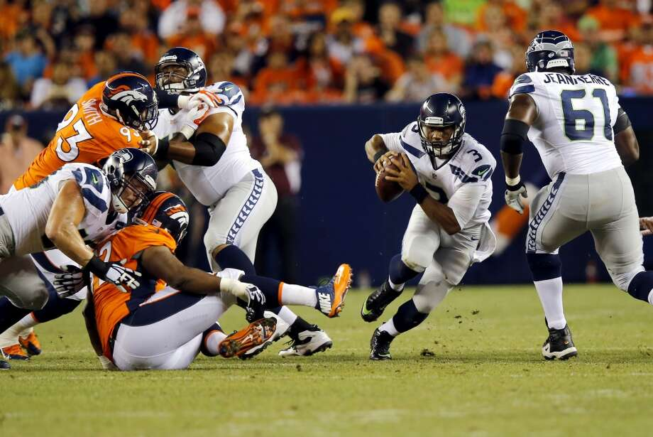 Seattle Seahawks quarterback Russell Wilson (3) scrambles against the Denver Broncos during the first half of an NFL preseason football game, Thursday, Aug. 7, 2014, in Denver. (AP Photo/Jack Dempsey) Photo: Jack Dempsey, AP