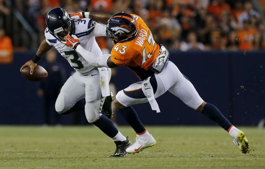 Seattle Seahawks quarterback Russell Wilson (3) has his face masked pulled by Denver Broncos strong safety T.J. Ward (43) during the first half of an NFL preseason football game, Thursday, Aug. 7, 2014, in Denver. (AP Photo/Joe Mahoney) Photo: Joe Mahoney, AP