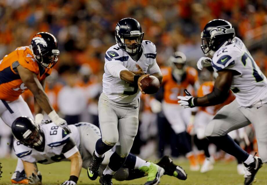 4Seattle Seahawks quarterback Russell Wilson (3) hands off to teammate Robert Turbin (22) during the first half of an NFL preseason football game against the Denver Broncos, Thursday, Aug. 7, 2014, in Denver. (AP Photo/Joe Mahoney) Photo: AP