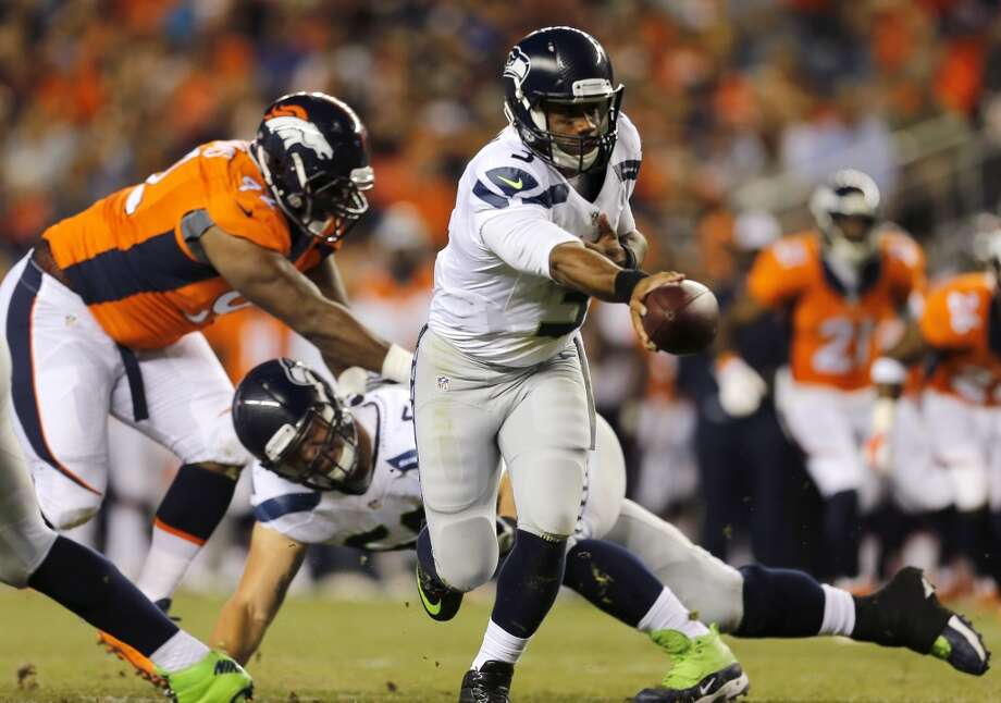 Seattle Seahawks quarterback Russell Wilson (3) hands off during the first half of an NFL preseason football game against the Denver Broncos, Thursday, Aug. 7, 2014, in Denver. (AP Photo/Joe Mahoney) Photo: AP