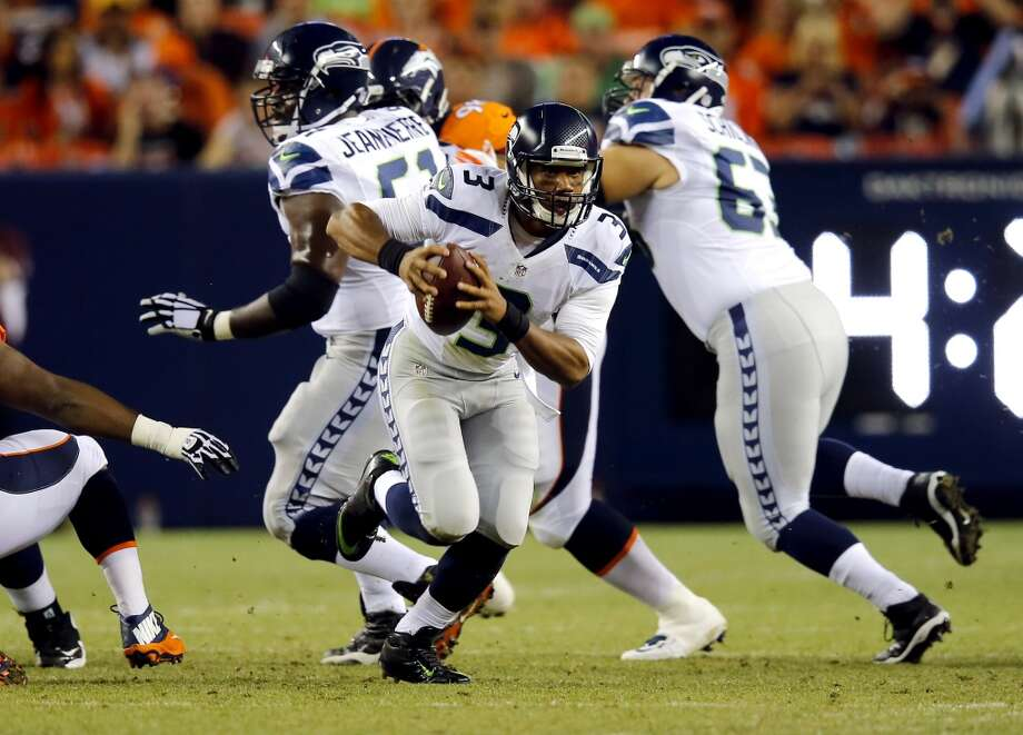 Seattle Seahawks quarterback Russell Wilson (3) scrambles against the Denver Broncos during the first half of an NFL preseason football game, Thursday, Aug. 7, 2014, in Denver. (AP Photo/Jack Dempsey) Photo: AP