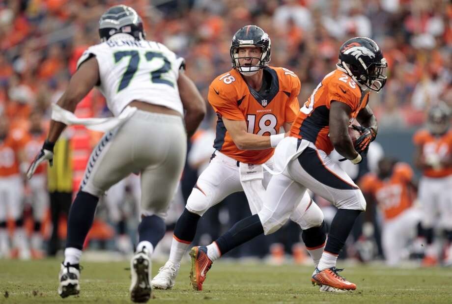 Denver Broncos quarterback Peyton Manning (18) ands off to Ronnie Hillman as Seattle Seahawks defensive end Michael Bennett defends during the first half of an NFL preseason football game, Thursday, Aug. 7, 2014, in Denver. (AP Photo/Joe Mahoney) Photo: AP