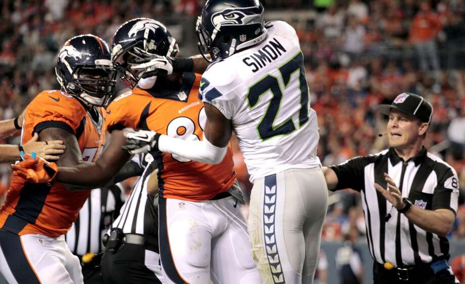 Seattle Seahawks cornerback Tharold Simon (27) punches Denver Broncos tight end Gerell Robinson (89) during the second half of an NFL preseason football game, Thursday, Aug. 7, 2014, in Denver. Simon was ejected. (AP Photo/Joe Mahoney) Photo: Joe Mahoney, AP