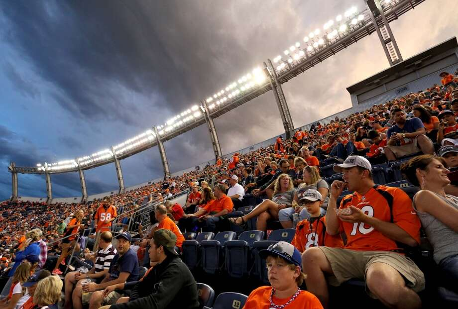 Fans wait out a lightning delay during the first half of an NFL preseason football game between the Denver Broncos and the Seattle Seahawks, Thursday, Aug. 7, 2014, in Denver. (AP Photo/Brennan Linsley) Photo: AP