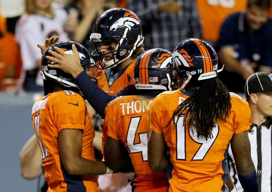Denver Broncos quarterback Brock Osweiler, rear, celebrates with Jordan Norwood (11) after Norwood scored a touchdown against the Seattle Seahawks during the second half of an NFL preseason football game, Thursday, Aug. 7, 2014, in Denver. (AP Photo/Joe Mahoney) Photo: AP